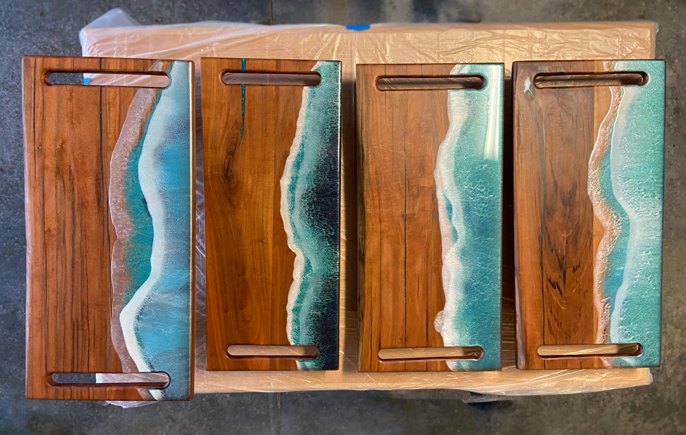 Four homemade charcuterie boards with cherry wood and epoxy designed to look like ocean waves