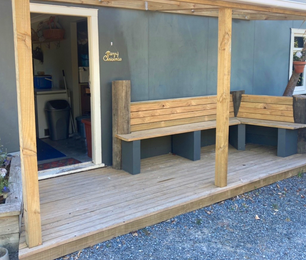 Covered porch with built-in benches built by Sam during the pandemic