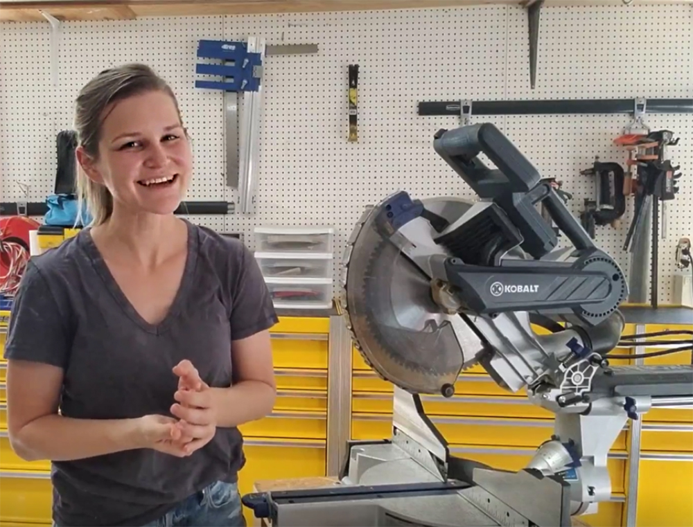 Emilee stands in a workshop with tool benches, tools and a saw