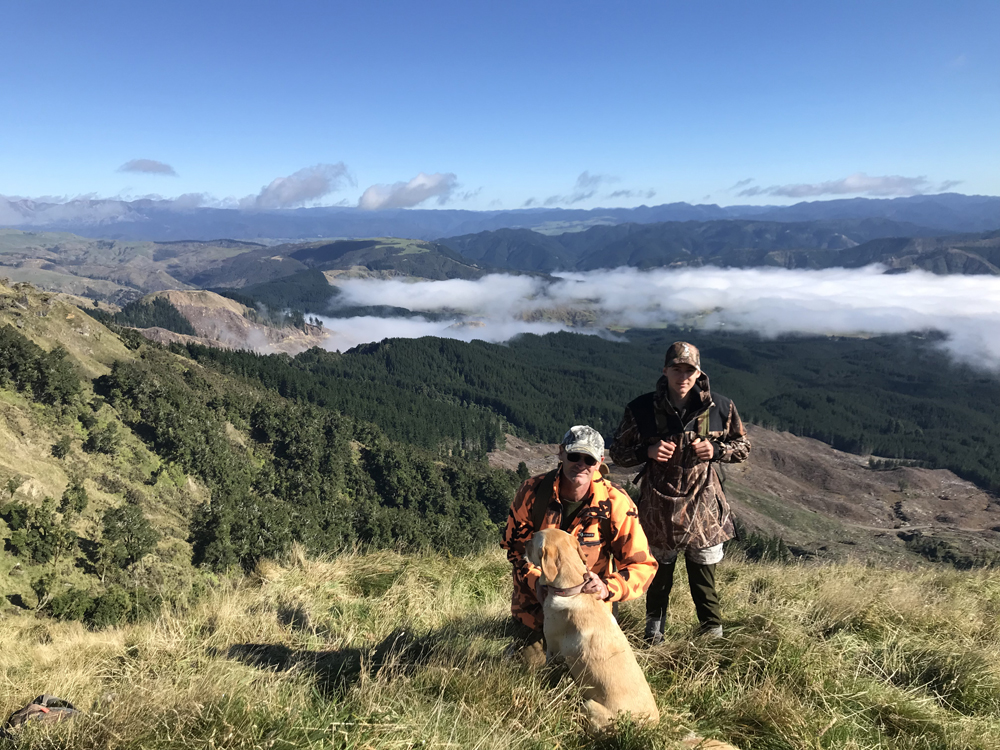 Sam and his son Max in front of a beautiful view from the top of one of Rayonier's Hawke's Bay, New Zealand, forests