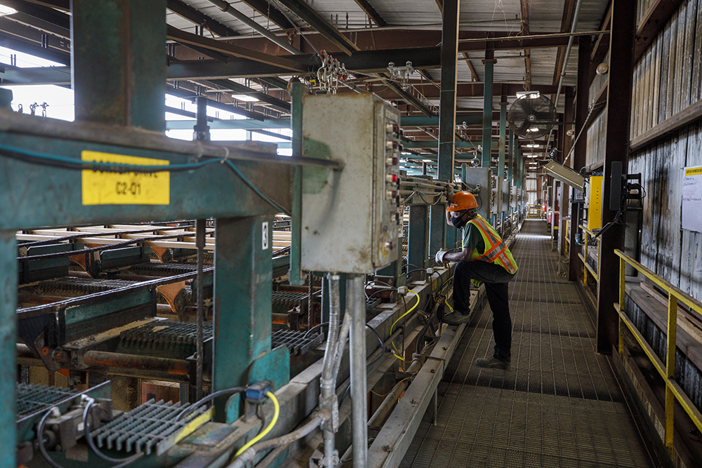 West Fraser employee watches boards move through the mill